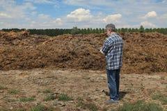 Agricoltore e mucchio di sterco nel campo Fotografia Stock Libera da Diritti