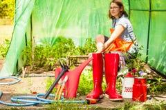 Agricoltore e strumenti di giardinaggio femminili in giardino Immagine Stock