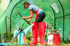 Agricoltore e strumenti di giardinaggio femminili in giardino Fotografie Stock