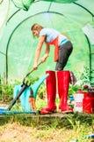 Agricoltore e strumenti di giardinaggio femminili in giardino Immagini Stock