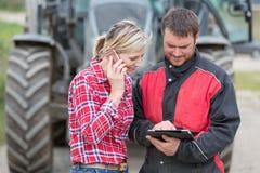 Agricoltore e tecnico che lavorano con lo Smart Phone e la compressa Immagini Stock