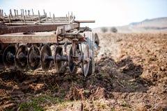 Agricoltore e trattore che arano in un campo Fotografie Stock Libere da Diritti