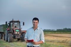 Agricoltore e trattore nel campo Immagini Stock