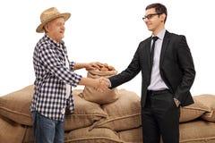 Agricoltore e un uomo d'affari che stringe le mani Fotografia Stock