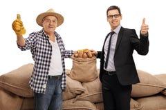 Agricoltore ed uomo d'affari che danno i pollici su Immagini Stock
