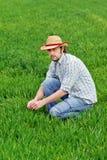 Agricoltore Examines e giovane campo di coltivazione del grano di comandi Immagine Stock