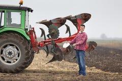 Agricoltore felice accanto all'aratro Immagine Stock Libera da Diritti