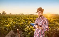 Agricoltore felice che fa le note davanti al paesaggio del campo Fotografia Stock
