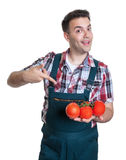 Agricoltore felice che indica il suo i pomodori freschi dell'azienda agricola Immagine Stock