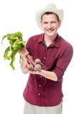 Agricoltore felice che mostra il raccolto della barbabietola su un bianco Immagine Stock