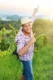 Agricoltore felice che si rilassa fra le file dell'uva Immagini Stock Libere da Diritti