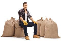 Agricoltore felice che si siede sui sacchi della tela da imballaggio Immagine Stock