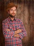 Agricoltore felice che sta sul fondo di legno rustico Fotografie Stock