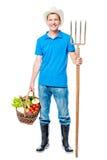 Agricoltore felice con le forcelle ed il raccolto delle verdure su un bianco Fotografie Stock Libere da Diritti