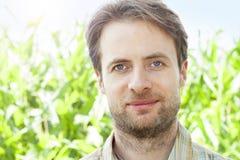 Agricoltore felice davanti al suo campo di grano Immagine Stock