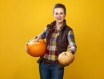 Agricoltore felice della giovane donna su fondo giallo che mostra le zucche Fotografia Stock Libera da Diritti