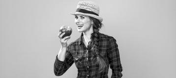 Agricoltore felice della giovane donna su fondo giallo con una mela Fotografia Stock Libera da Diritti