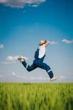 Agricoltore felice nel grano contro cielo blu con le nuvole bianche Fotografia Stock