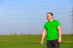 Agricoltore felice (uomo d'affari) che sta nel giacimento di grano sopra il tur del vento Immagini Stock