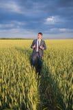 Agricoltore felice, uomo d'affari, stante nel giacimento di grano Immagini Stock Libere da Diritti