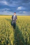 Agricoltore felice, uomo d'affari, stante nel giacimento di grano Immagine Stock