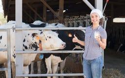 Agricoltore femminile allegro che sta con nel capannone della mucca Immagine Stock