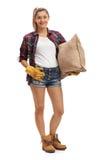 Agricoltore femminile allegro che tiene un sacco della tela da imballaggio Fotografia Stock Libera da Diritti