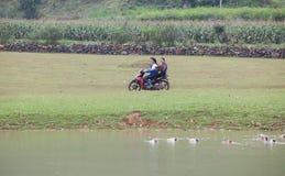 Agricoltore femminile asiatico che va lavorare al campo in motociclo Fotografia Stock