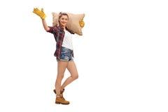 Agricoltore femminile che cammina con un sacco e un ondeggiamento della tela da imballaggio Fotografie Stock Libere da Diritti