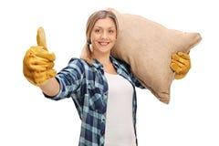 Agricoltore femminile che dà pollice su e che porta un sacco Fotografie Stock Libere da Diritti