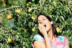 Agricoltore femminile che mangia frutta dal pero Fotografia Stock Libera da Diritti