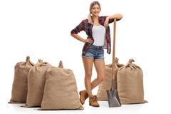 Agricoltore femminile che posa con i sacchi della tela da imballaggio e della pala Immagini Stock