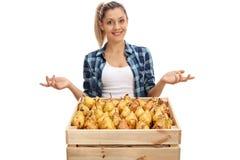 Agricoltore femminile che posa con la cassa e che gesturing con le mani Fotografie Stock