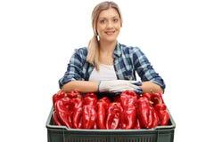 Agricoltore femminile che posa con una cassa piena dei peperoni Immagini Stock
