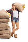 Agricoltore femminile che si appoggia mucchio dei sacchi della tela da imballaggio e che tiene sacco o Fotografia Stock