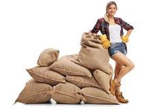 Agricoltore femminile che si appoggia un mucchio dei sacchi della tela da imballaggio Fotografia Stock