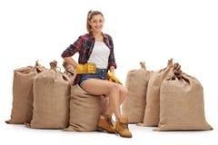 Agricoltore femminile che si siede su un mucchio dei sacchi della tela da imballaggio Immagini Stock