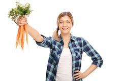 Agricoltore femminile che tiene un mazzo di carote Fotografia Stock