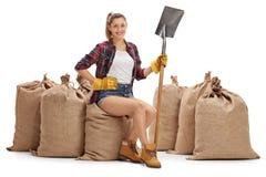 Agricoltore femminile che tiene una pala e che si siede sui sacchi della tela da imballaggio Fotografia Stock Libera da Diritti