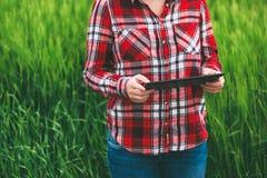 Agricoltore femminile che utilizza il computer della compressa nel campo del raccolto dell'orzo Fotografie Stock
