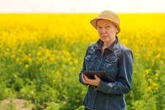 Agricoltore femminile che utilizza il computer della compressa nel giacimento del seme di ravizzone Immagine Stock Libera da Diritti