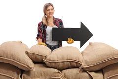 Agricoltore femminile dietro i sacchi della tela da imballaggio con una freccia Fotografie Stock