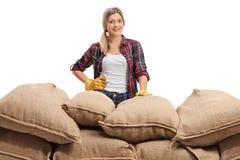 Agricoltore femminile dietro un mucchio dei sacchi della tela da imballaggio Immagine Stock Libera da Diritti
