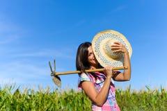 Agricoltore femminile felice con l'estirpazione della zappa in un campo di grano Immagine Stock Libera da Diritti