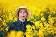 Agricoltore femminile nel giacimento agricolo coltivato seme di ravizzone del seme oleifero Immagini Stock