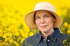 Agricoltore femminile nel giacimento agricolo coltivato seme di ravizzone del seme oleifero Fotografia Stock
