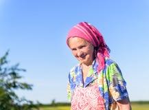 Agricoltore femminile senior sorridente ai campi verdi Fotografia Stock