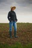 Agricoltore femminile Standing sul suolo agricolo fertile della terra dell'azienda agricola Fotografia Stock