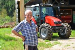 Agricoltore fiero che sta davanti al suo trattore Immagine Stock