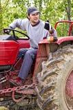 Agricoltore giovane che guida il suo trattore e che fa segno giusto Fotografia Stock